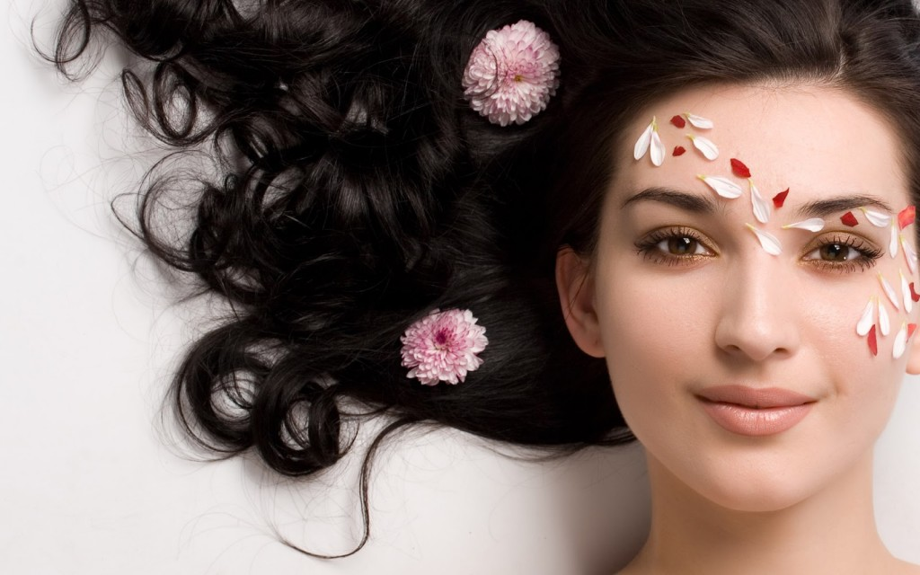 Portrait of Fresh and Beautiful brunette woman laying on grey  background around pink flowers